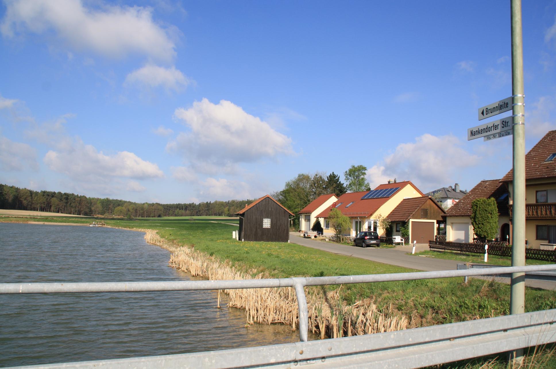 Jenseits, nördlich des Weihers, soll in der Brunnleite der zweite Standort der Firma Schweiß/Löttechnik Gumbrecht entstehen. Die Gewerbefläche erstreckt sich hinter der Häuserreihe bzw den Bäumen.