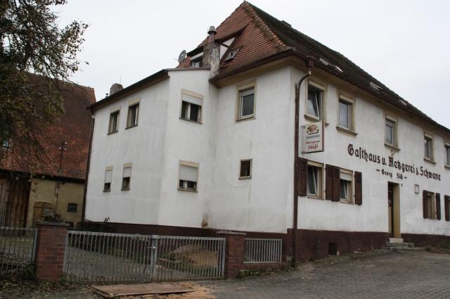 """Das denkmalgeschützte barocke Gebäude """"Zur Schwane"""", um 1760 erbaut. Der seitliche Anbau, ursprünglich war dort der """"Abtritt"""", also die Freilufttoilette, wird abgerissen, das Gebäude damit """"rückgebaut"""". Die Scheune dahinter wird künftig als Wohnraum und Versorgungsbereich genutzt. Auf dem Vorplatz entsteht eine Grünfläche."""