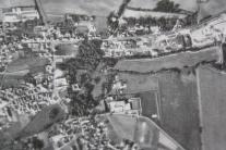 Ein Ausschnitt aus einer Luftaufnahme von Oktober 1979 zeigt die Ortsdurchfahrt mit Nordkreuzung. Der Laubbaumbestand gehört zum Schlossareal. In der Mitte ist der quadratische Schlossbau deutlich zu erkennen, schräg darüber der helle hufeisenförmige Ökonomie-Komplex direkt an der Höchstadter Straße. Westlich des oberen Baumbestandes gut sichtbar ist der leere Bereich der ehemaligen Gärtnerei mit dem Gärtnerhaus nahe der Nordkreuzung. Dieser Teil wurde dann später Baugebiet. (Weisendorfer Chronik, 1988)