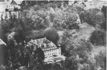 Eine Luftaufnahme vom Schloss mit Blick von Süden vor dem 2. Weltkrieg: Im oberen Teil des Fotos schimmert durch den dichten Baumbestand die Erlanger Strasse. Links unten verdecken die Bäume Zufahrt und Eingang zum Schloss. (Foto: privat)