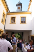 Blick zum Schlosstor im Norden: Der Innenhof mit saniertem Glockenturm und plaudernden Gästen. Im Vordergrund