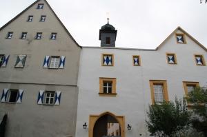 Die Nordfront des Schlosses. Lnks das Hochschloss, der älteste Teil, rechts der neuere, bereits renovierte. Dazwischen das Schlosstor, bei dem man zur Erinnerung an die ehemalige Zugbrücke oben mit dem rechteckigen, gelben Rahmen den Bereich betont, in den die hochgezogene Brücke eingerastet ist.